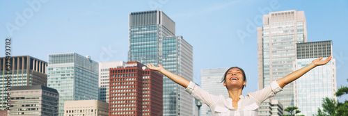 Fotomural Happy asian woman with open arms up to the sky breathing fresh air in city downtown buildings background