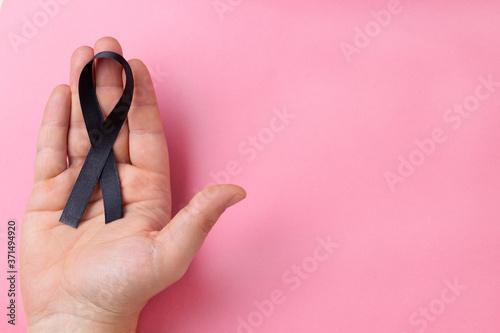Fotografia Hand holding black ribbon on a pink background..Melanoma.