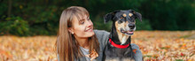 Young Caucasian Woman Lying On Ground Fall Leaves Hugging Dog. Owner Walking With Pet On Autumn Day. Best Friends Having Fun Outdoors. Friendship Of Human With Animal. Web Banner Header.