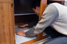 Man Placing Protective Liner Gray Sheet Inside On Wooden Cabinets With Hands In Kitchen Drawers