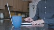 Smartly dressed man using the trackpad on a laptop on a kitchen counter while working from home with a mug of warm drink next to him close up