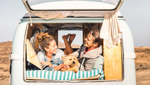 Hipster People With Cute Dog Traveling Together On Vintage Minivan - Wanderlust And Life Inspiration Concept With Hippie Couple On Mini Van Adventure Trip - Bright Warm Filter