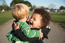 Happy Baby Boys Hugging Outdoors