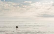 Hispanic Surfer Floating In Water