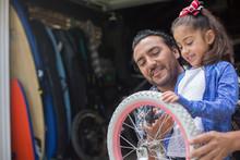 Hispanic Father Teaching Daughter To Repair Bicycle