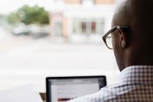 Black Man Using Laptop At Window