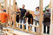 Volunteers Holding Framed Wall...