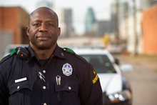 Portrait Of Police Officer Standing In Street In Front Of Squad Car Looking Towards Camera With Arms Behind His Back
