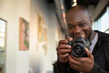 Portrait Of Smiling Young Man Standing In Hallway With Camera