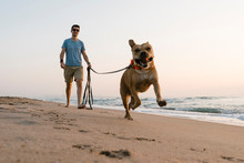 Man With His Dog Running At Beach During Dawn