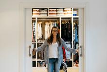 Smiling Woman Opening Doors Of...