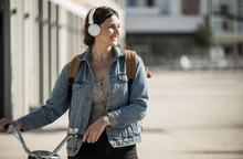 Smiling Woman Listening Music Through Headphones While Walking With Bicycle In City