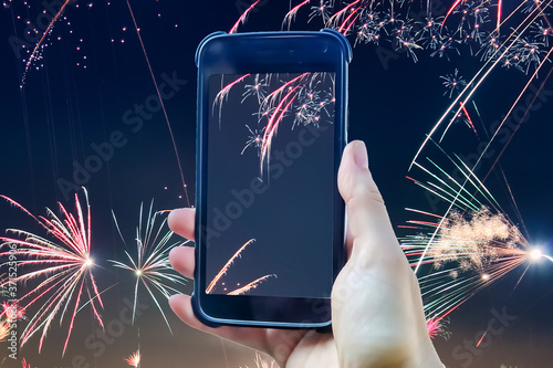 Leinwand Poster Fireworks composing of a female hand holding a smartphone taking a picture
