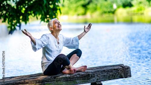 Obraz Beautiful mature woman enjoying peace and tranquility of the nature - fototapety do salonu