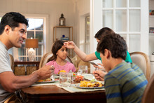 Hispanic Family Around The Dinner Table With The Daughter Feeling Ill, Mom Checking Her Temperature And Checking Cell Phone To Connect With Doctor