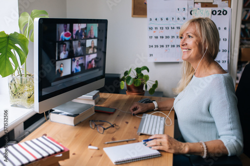 Canvas Smiling mature woman having video call via computer in the home office