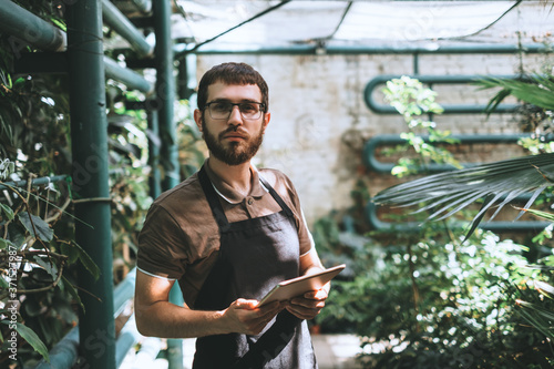 Portrait of young man gardener in glasses and apron with digital tablet working in a garden center for better quality control Fototapet