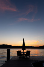 Silhouette Of Outdoor Chairs And A Table With An Umbrella On A Dock In Front Of A Colorful Sunset On A Lake With Mountains