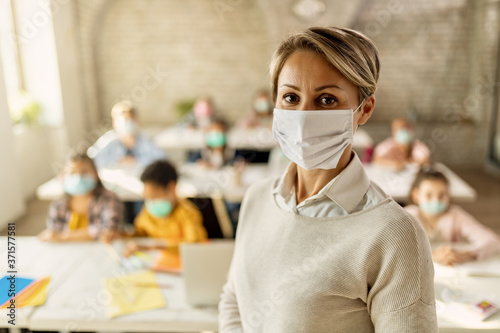 Fototapeta Elementary school teacher with protective face mask in the classroom