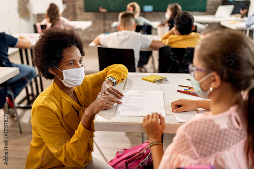 Fotografia Black teacher with a face mask explaining exam results to elementary student in the classroom