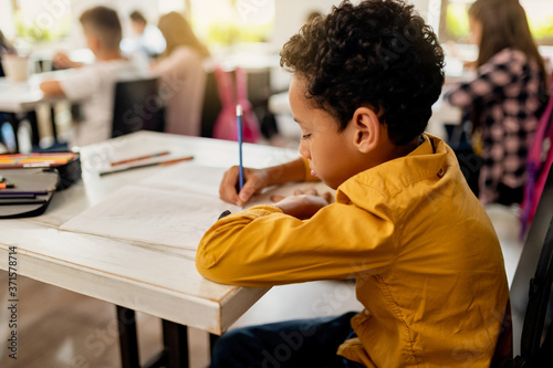 Carta da parati African American schoolboy writing at his desk in the classroom.