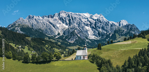 Photo Panorama of green meadows and parish church of Dienten with Hochkönig mountain on the background