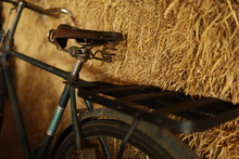 An Old Bicycle Is Placed Next To A Haystack, Reminiscent Of The