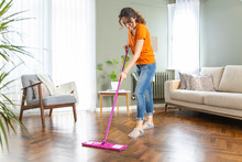 Young Housewife Cleaning Wooden Parquet Using Microfiber Mop Pad