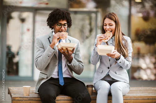 Leinwand Poster Smiling businessman and businesswoman with sandwiches sitting in front of the of