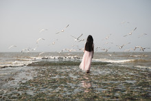 Woman Walking On The Beach In Long Dress With Flock Of Seagulls Near Ocean