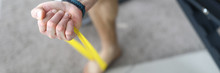 Close-up Of Person Exercising With Yellow Fitness Rubber Band. Man Training Arm At Home. Macro Shot Of Man Getting Stronger. Sport And Fit Body On Quarantine Concept