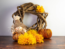 Fall Themed Wooden Wreath With Yellow And Orange Artificial Flowers, An Orange Pumpkin And A Mini Scarecrow Arranged On A Wooden Surface With A White Wall Behind.  Autumn, Halloween, Thanksgiving.