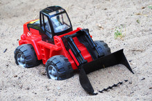 A Red And Black Children's Bulldozer Stands On The Sand . Excavator