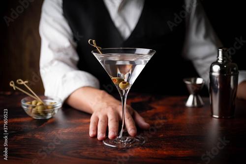 Fototapeta bartender serving martini in glass at bar obraz