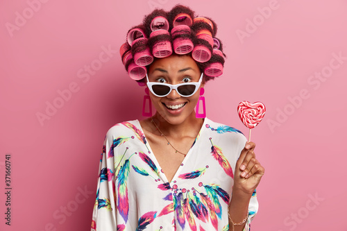 Canvastavla Beautiful cheerful young woman in trendy sunglasses, wears hair curlers, makes hairstyle, dressed in domestic gown, holds lollipop