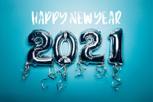 Happy New Year Words And Balloon Bunting For Celebration Of New Year 2021 Made From Silver Number Balloons. Holiday Party Decoration Or Postcard Concept, On Blue Background
