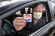"Leinwandbild Motiv Man holding an ""I voted today"" sticker after voting wearing a face mask to prevent the spread of coronavirus"
