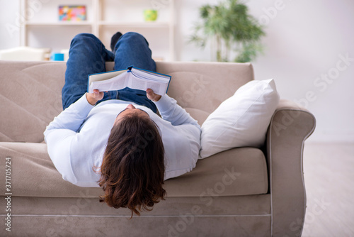 Foto Young male student preparing for exams at home
