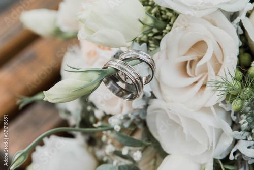 Fototapeta wedding rings on bouquet of roses.