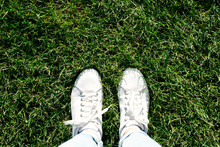 Legs In White Sneakers And Blue Jeans Are On The Grass.