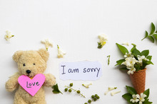 I Am Sorry ,i Love You On Pink Paper Hearts Message Card Handwriting With Teddy Bear ,jasmine Flowers In Cone Arrangement Flat Lay Style On Background White