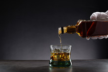 White Gloved Hand Pouring Whisky Into A Glass With Ice On Dark Background, With Copy Space.