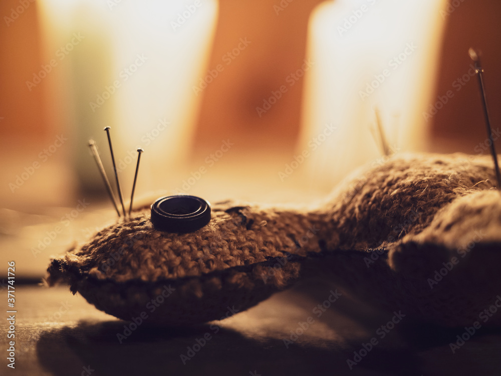 Fototapeta Rag doll voodoo pierced with needles, lying on a wooden table surrounded by burning candles, close-up. The concept of divination, rite, ritual and black magic. Harming people with a voodoo doll