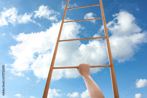 Woman climbing up wooden ladder against blue sky with clouds, closeup Wallpaper Mural