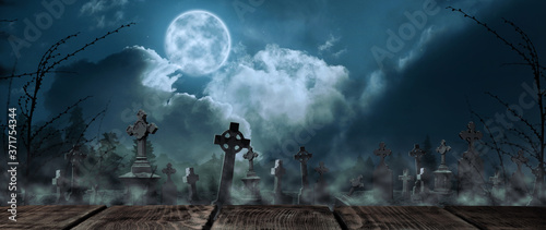 Fotografie, Obraz Wooden surface and misty graveyard with old creepy headstones under full moon