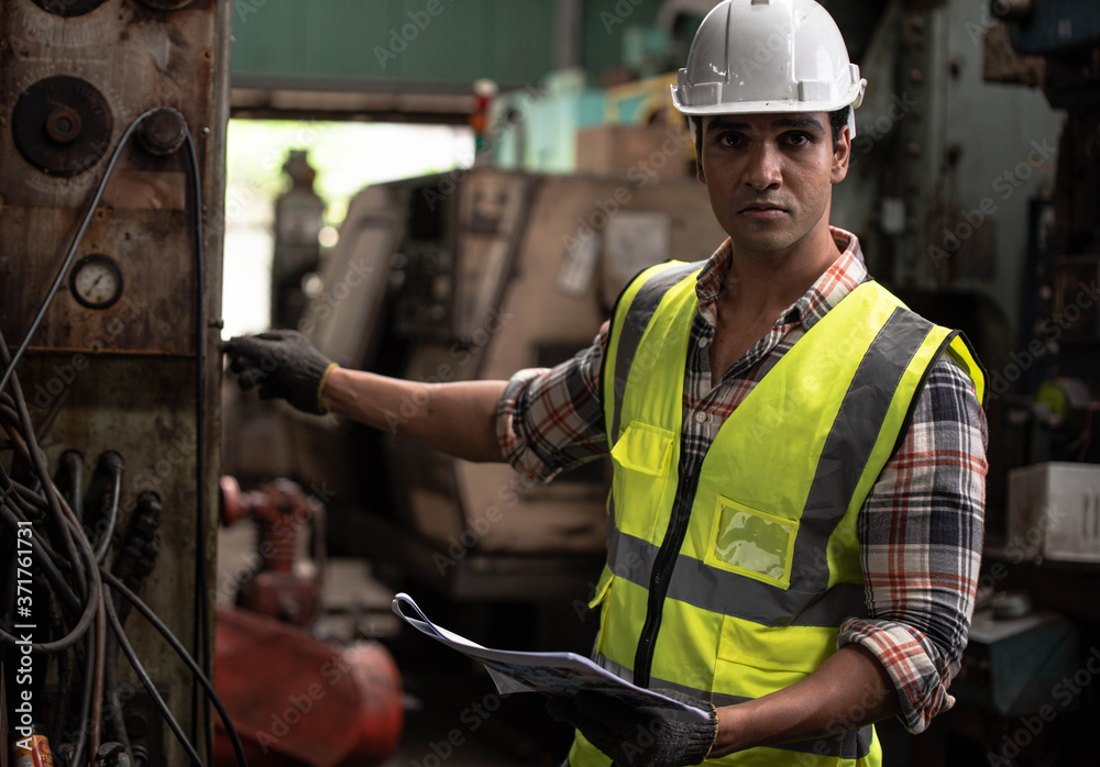 Fototapeta Portrait of young handsome technician man or industrial worker with hard hat or helmet and vest jacket working electronic machinery and mechanical engineering in Factory of manufacturing place