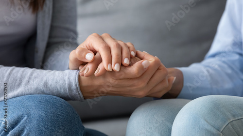 Obraz na plátne Close up young woman covering hands of mature senior mother, asking for forgiveness, feeling guilty, apologizing indoors