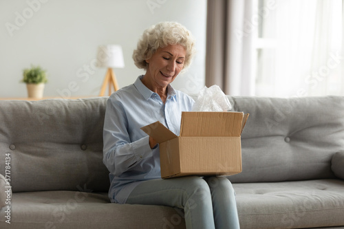Fototapeta Positive middle aged older woman sitting on couch with carton box on laps, feeling curious about ordered wished item from website, smiling female client satisfied with fast courier delivery service