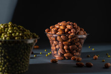 Pinto Beans In Glass Pot With Blurry Mung Bean Image Black Background