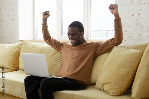 Photo Happy black man excited getting good news notification at home